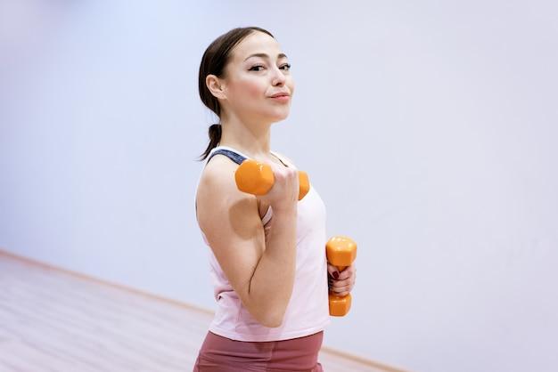 Heureuse femme caucasienne faisant du fitness avec des haltères à la maison