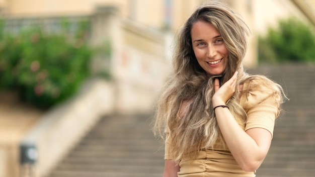 Heureuse femme caucasienne en robe avec vue sur barcelone en arrière-plan, espagne