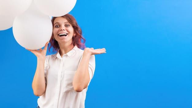 Heureuse femme caucasienne souriante avec des ballons blancs