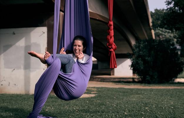 Heureuse femme caucasienne utilisant son tissu extensible aérien comme hamac tout en s'entraînant dans un parc