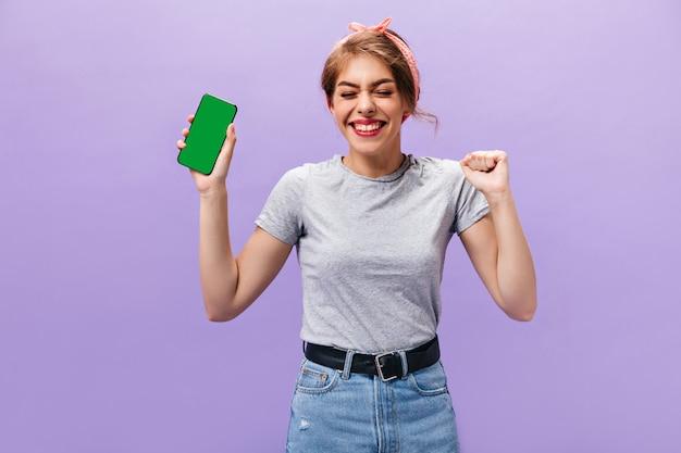 Heureuse femme en chemise grise tient le téléphone. fille joyeuse avec bandeau rose en jupe en jean avec ceinture noire s'amuse sur fond isolé.
