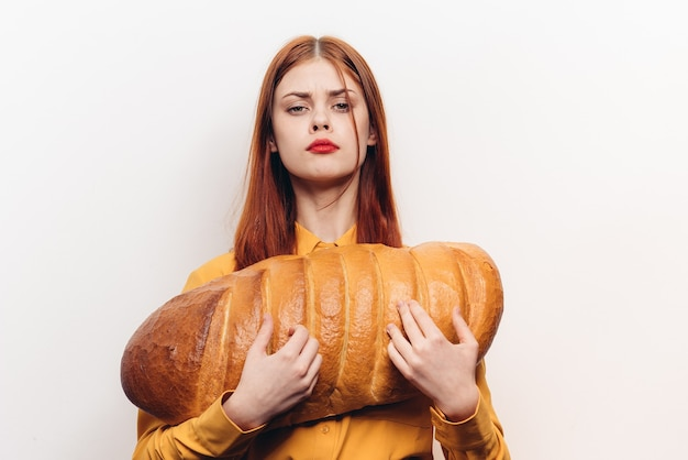 Heureuse femme en chemise jaune tient un gros pain dans ses mains et sourit.