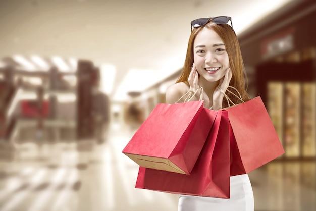 Heureuse femme chinoise avec des sacs en papier rouge sur le centre commercial