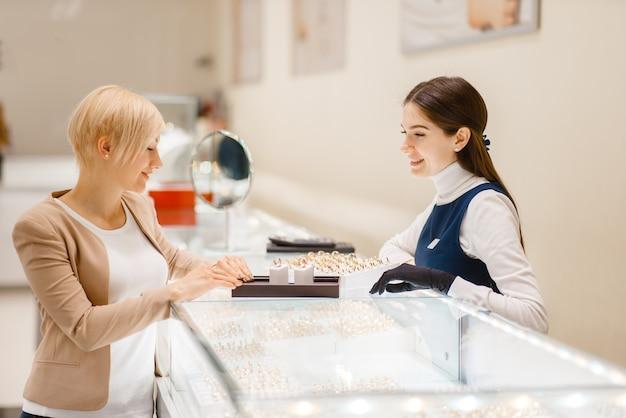 Heureuse femme choisissant des alliances en bijouterie.