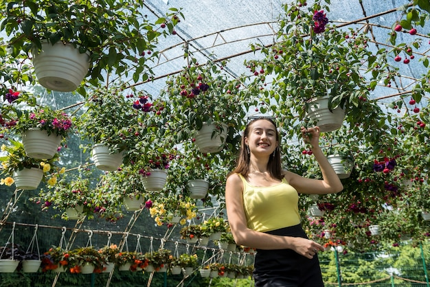 Heureuse femme choisit des fleurs dans une serre. botanique