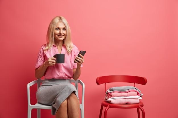 Heureuse femme de cinquante ans tient un téléphone portable et une tasse de thé sur les réseaux sociaux tout en passant du temps libre à la maison, assise sur une chaise confortable, elle aime seule la communication en ligne. concept de style de vie