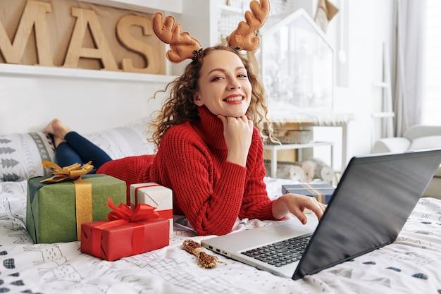 Heureuse femme couchée dans son lit avec des cadeaux