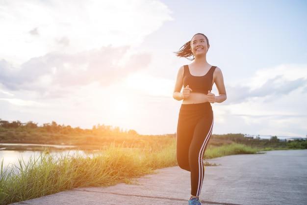 Heureuse femme coureur s'exécute dans l'exercice de jogging du parc.