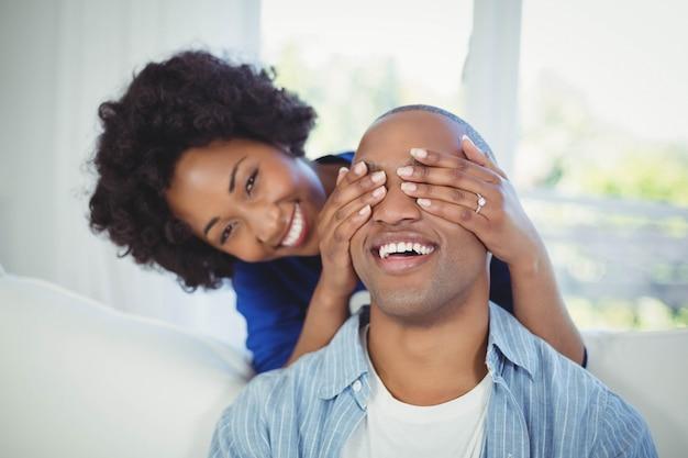 Heureuse femme couvrant ses yeux d'homme avec les mains dans le salon
