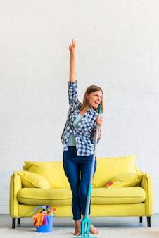 Heureuse femme dansant avec une vadrouille à la maison