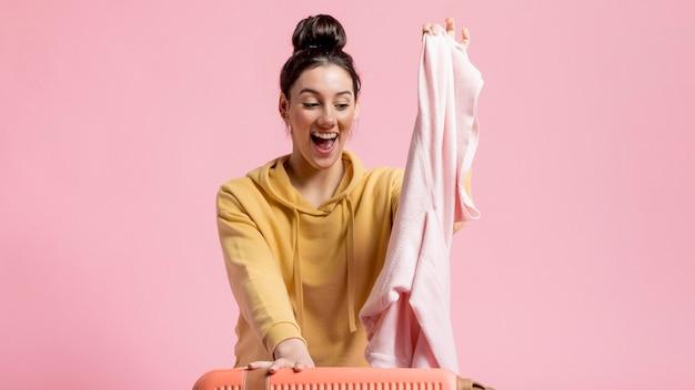Heureuse femme déballant ses bagages