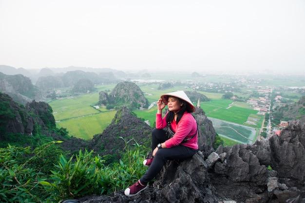 Heureuse femme debout au sommet d'une montagne à la grotte de mua, ninh binh, vietnam au soir, le sujet est flou, discret et bruyant.