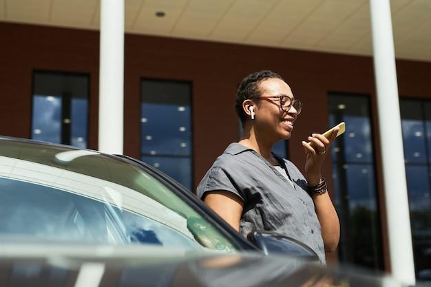 Heureuse femme debout près de la voiture dans la ville et parlant au téléphone portable