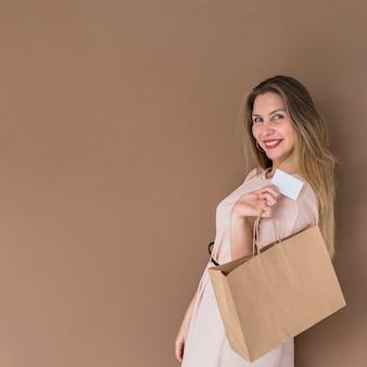 Heureuse femme debout avec sac à provisions et carte de crédit