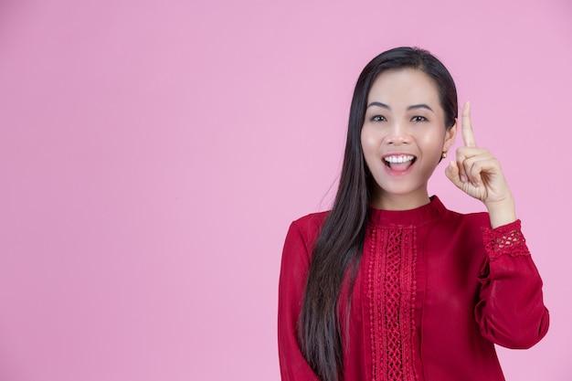 Heureuse femme debout avec son doigt pointé