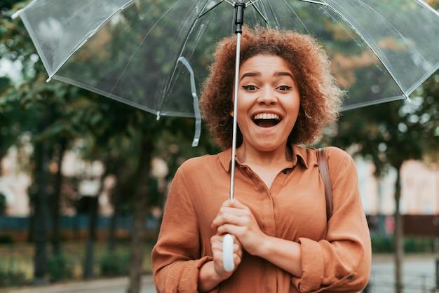 Heureuse femme debout sous son parapluie à l'automne