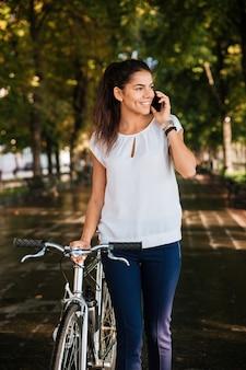 Heureuse femme décontractée, parler au téléphone et marcher à vélo dans le parc de la ville