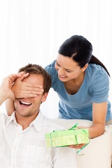 Heureuse femme donnant un cadeau à son petit ami tout en cachant ses yeux