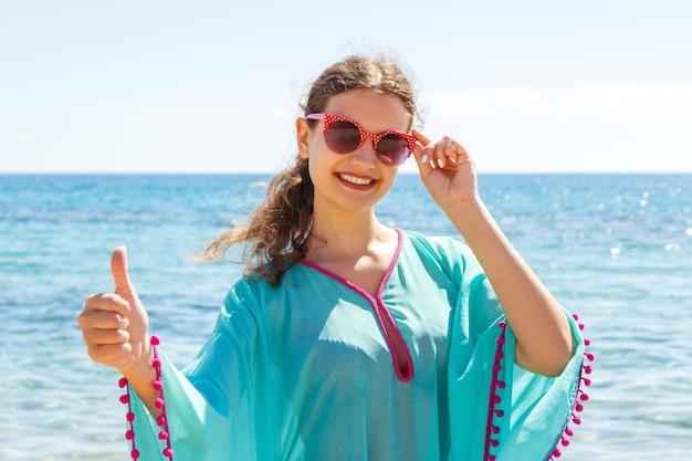 Heureuse femme donnant le pouce en l'air succès main signe à l'extérieur sur la plage