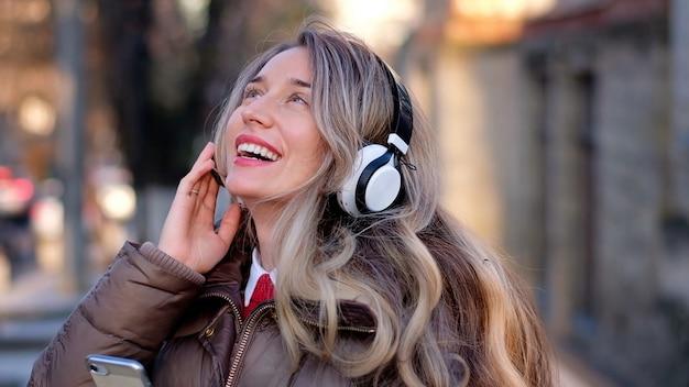 Heureuse femme écoutant de la musique sur un casque sans fil
