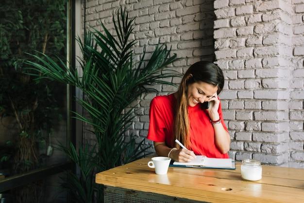 Heureuse femme écrivant le calendrier dans le journal parlant sur téléphone mobile