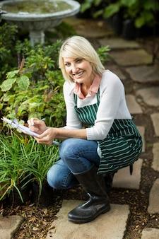 Heureuse femme écrivant sur le presse-papiers tout en examinant les plantes