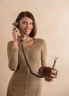 Heureuse femme élégante parlant sur téléphone rétro
