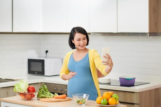 Heureuse femme enceinte à l'aide de l'enregistreur de commande vocale sur smartphone