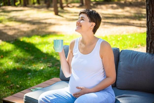 Heureuse femme enceinte assise dans le parc d'été