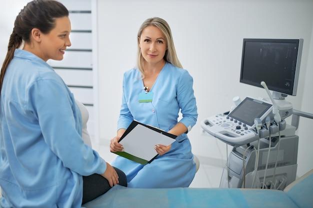 Heureuse femme enceinte aux cheveux noirs ayant un examen médical régulier avec une femme médecin à une clinique moderne. consultation de gynécologie.