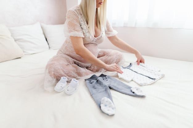 Heureuse femme enceinte caucasienne blonde regardant les vêtements de bébé assis sur le lit, les jambes croisées dans la chambre.