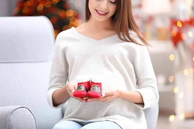 Heureuse femme enceinte avec des chaussons pour bébé à la maison