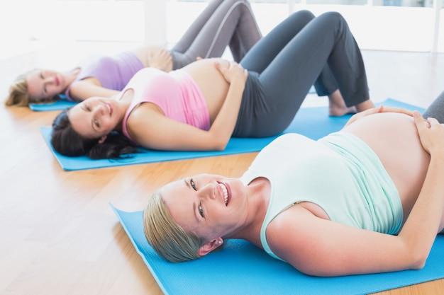 Heureuse femme enceinte en cours de yoga allongé sur des nattes