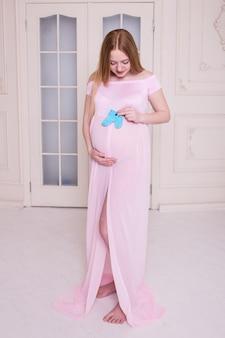 Heureuse femme enceinte debout à la maison avec des chaussons bleus à la main.