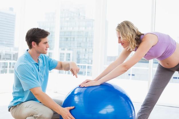 Heureuse femme enceinte exerçant avec entraîneur et ballon