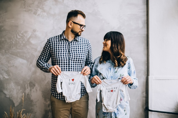 Heureuse femme enceinte huges son mari chez eux, élégant couple marié, les gens attendent un enfant, belle femme enceinte, parents heureux, amour en famille