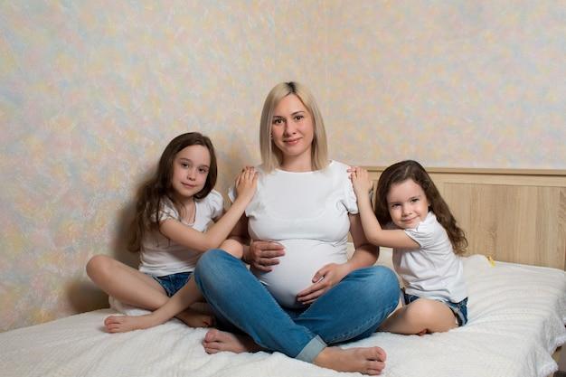 Heureuse femme enceinte avec ses filles, assise sur le lit à la maison. famille heureuse dans l'isolement. les enfants adorent leur mère