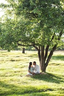 Heureuse femme enceinte avec son mari au coucher du soleil