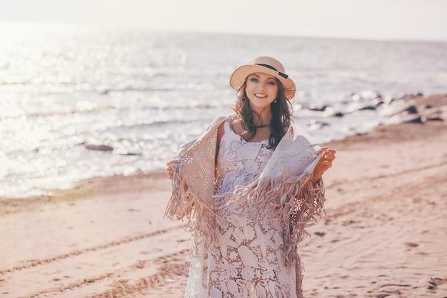 Heureuse femme enceinte souriante sur la plage