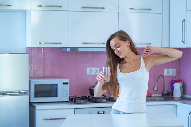 Heureuse femme endormie qui s'étend et boit un verre d'eau du matin purifiée propre tôt le matin après son réveil dans la cuisine à la maison. début et début d'une nouvelle bonne journée