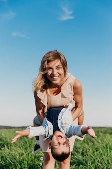 Heureuse femme avec enfant jouant ensemble dans le champ