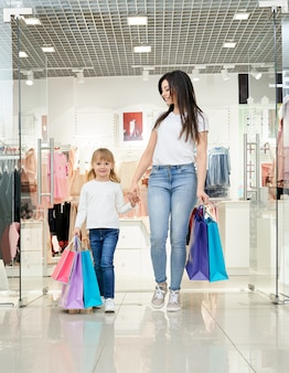 Heureuse femme et enfant tenant des sacs à provisions en magasin.