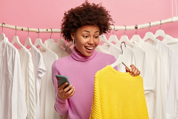Heureuse femme ethnique examine la collection de vêtements dans la salle d'exposition, détient un chandail tricoté jaune sur cintre, utilise un téléphone mobile