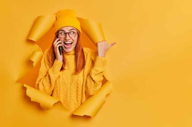 Heureuse femme européenne rousse joyeuse porte un chapeau et un pull chaud a une conversation positive via le smartphone pointe le pouce sur un espace vide.
