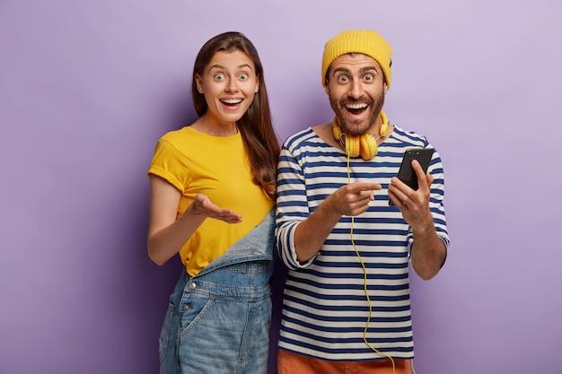 Heureuse femme européenne et son petit ami utilisent un gadget moderne pour envoyer des messages texte dans le chat en ligne, regardez avec des expressions heureuses et surpris, utilisez des écouteurs stéréo