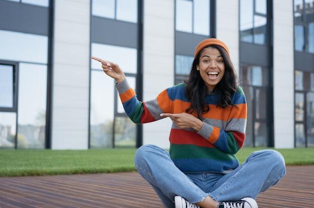 Heureuse femme excitée pointant les doigts de côté et assis à l'extérieur