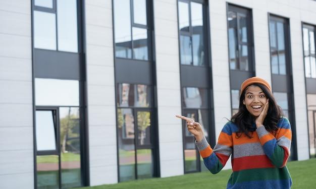 Heureuse femme excitée pointant avec la main sur l'espace de copie, debout à l'extérieur