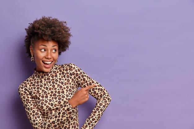 Heureuse femme féminine avec une coiffure frisée, pointe l'index vers le côté droit, discute de la belle promo, donne la direction de l'espace de copie, porte un col roulé léopard