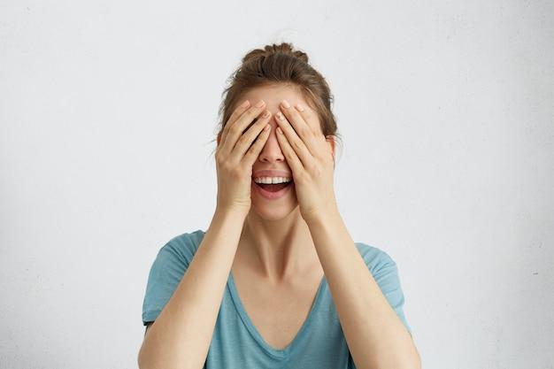 Heureuse femme fermant les yeux avec les mains va voir la surprise, debout et souriant en prévision de quelque chose de merveilleux