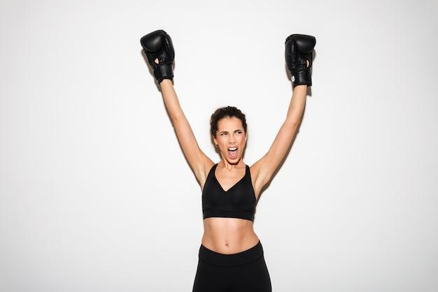 Heureuse femme fitness brune frisée hurlant se réjouit